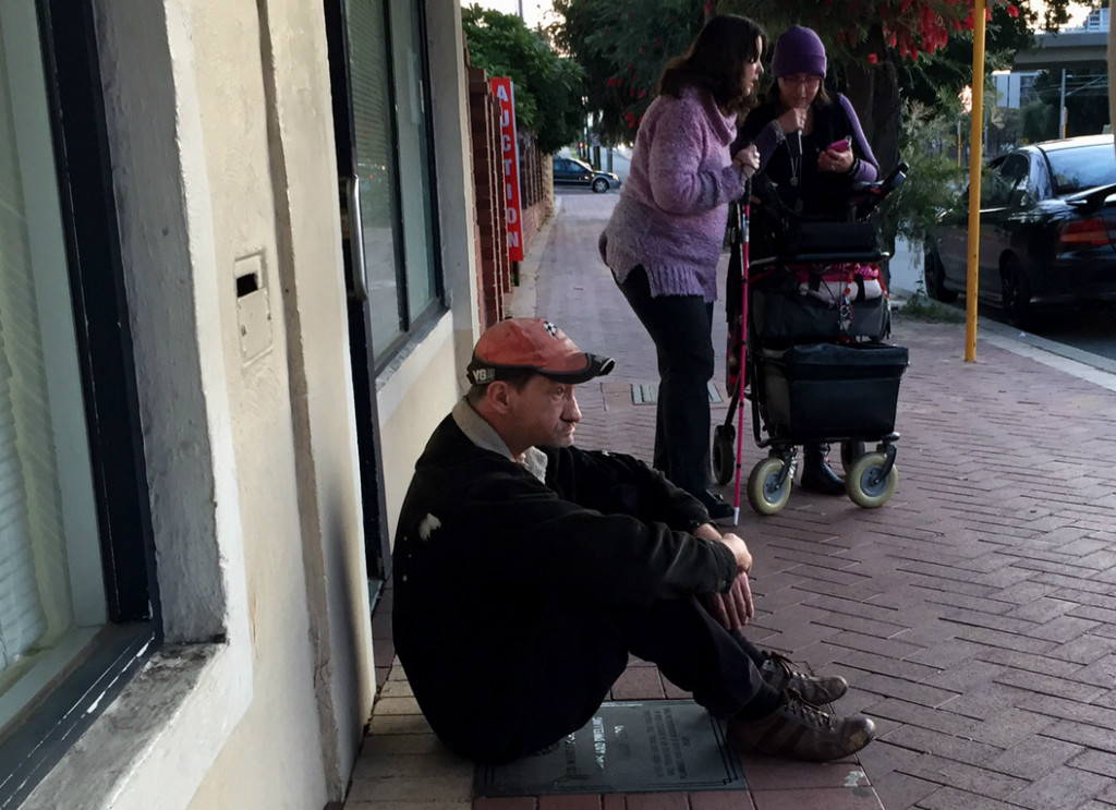 Man sits waiting for a homeless shelter to open (Photo by Josh Low)