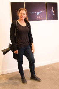 """Janet Craig, photographer, in front of some of her """"Do It For Yourself and Help Somebody Else' portraits"""