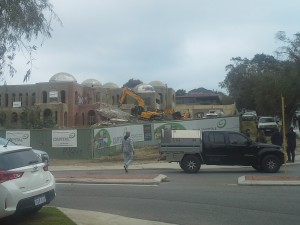 Two excavators work together to tear apart the 6 year old building.