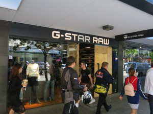 People walk by the boarded up entrance to the G-Star Raw clothing store.